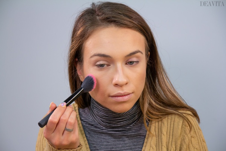 Apply blush on the cheeks with a fluffy angled brush