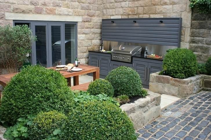 small backyard with outdoor kitchen and dining furniture