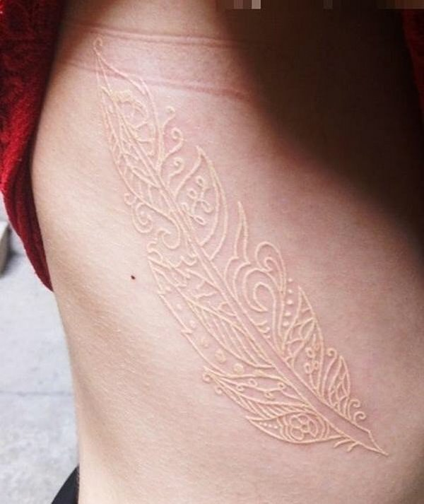 tribal style white ink feather tattoo on ribs